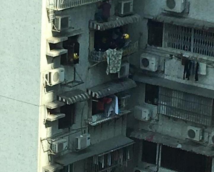 北京街有男子危站大廈簷篷被救